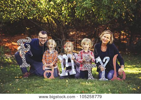 a cute family posing with letters made of wood in a park toned with a retro vintage instagram filter effect app or action