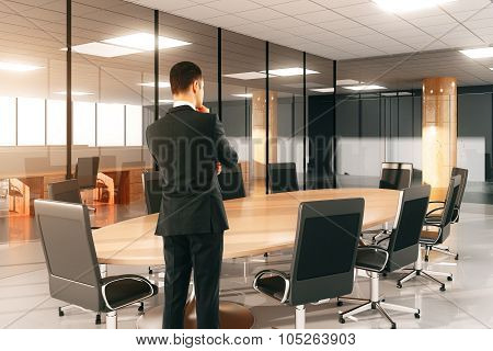 Businessman Watching On Round Conference Table With Chairs In The Office
