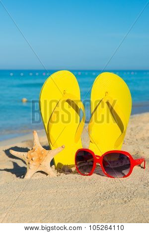 Travel By Sea. Beach Vacation. Red Sunglasses And Yellow Flip-flops On Sandy Seashore.