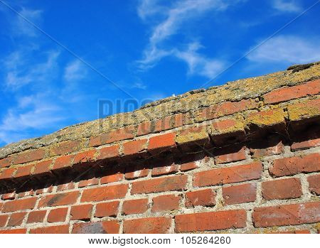 Upper Part Of The Stone Wall Of Bricks Against A Bright Blue Sky