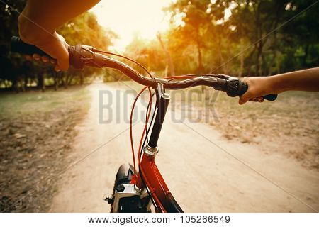 Hands of a man on bicycle handlebars.