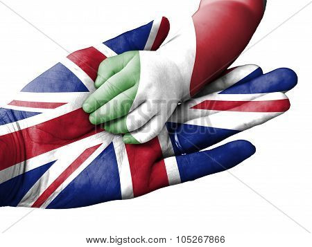 Adult Man Holding A Baby Hand With United Kingdom And Italy Flags Overlaid. Isolated On White
