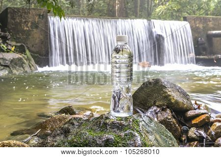 Plastic bottle with waterfall background at tropical forest