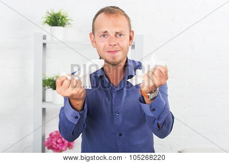 Young businessman working in the office, very concerned, a panic, crumpled paper