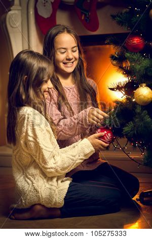 Two Cute Girls Sitting On Floor And Decorating Christmas Tree