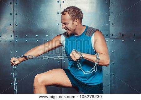 Sportsmen. fit male stands and tear metal chain , concept  fitness workout strenght power.