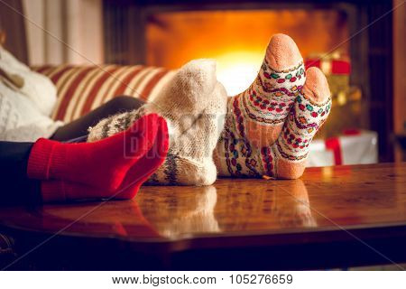 Closeup Of Family Warming Feet At Fireplace