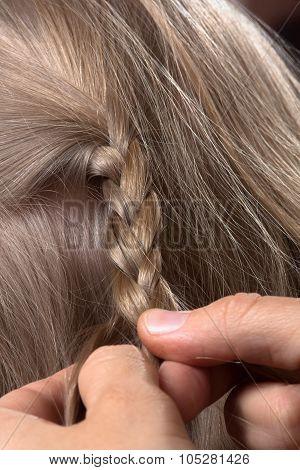 Closeup Of A Hairdresser Braiding Hair In Trendy Plait