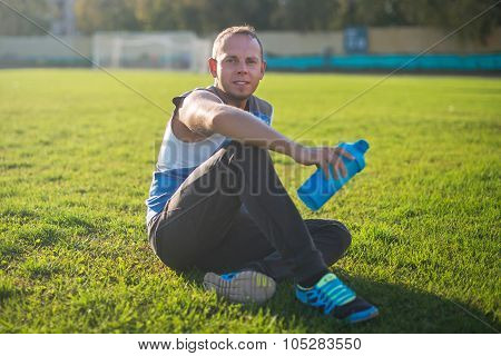 Sporting an attractive man sitting on grass and rests in the stadium, keeps shaker, sunny day