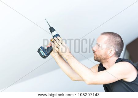Man Drilling In Ceiling