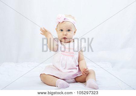 baby girl  playing in the white studio surroundings