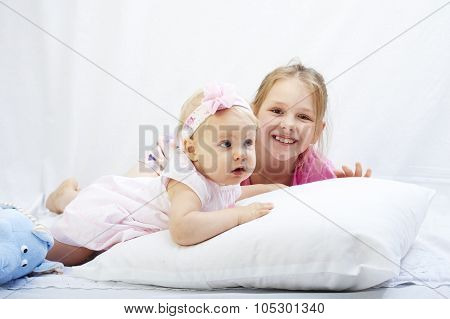 cute little sister play with  newborn on a white background