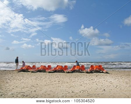 People resting by orange pedal boats