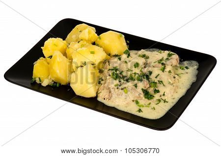 Slices of pork tenderloin with potatoes stewed in cream saucem - served on the black plate. isolated