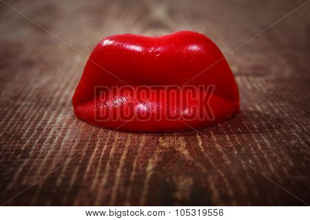 Wax lips on a wooden background. Shallow focus on bottom of lips