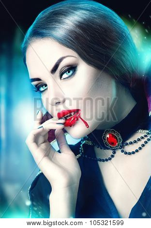 Vampire Halloween  Woman portrait. Beauty Sexy Vampire Girl with blood on her mouth looking at camera. Fashion Art design. Attractive model girl in Halloween costume and make up