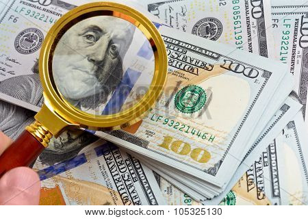 Hundred dollar banknotes under magnifying glass