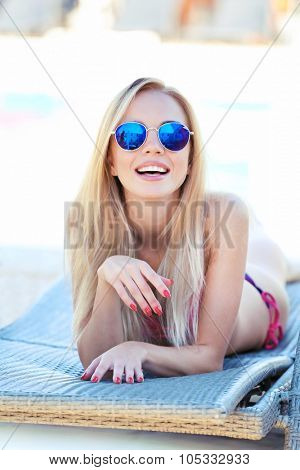 Young girl relaxing on chaise-lounge