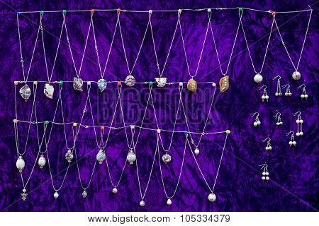 White Meerschaum Necklaces Hanging On Purple Cloth