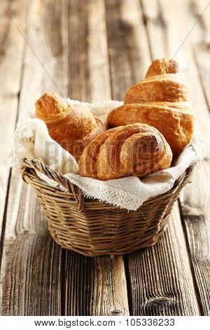 Tasty Croissants In Basket On Brown Wooden Background