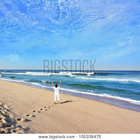 Middle-aged woman dressed in white doing yoga. Huge beautiful beach on the Atlantic coast. The seaside resort of Sintra