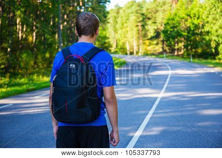 Hiking Concept - Man With Backpack Walking On Forest Road