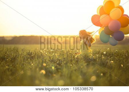 Happy girl with balloons in the field