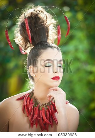 Beautiful young woman portrait with red hot spicy peppers around the neck and in hair, fashion model