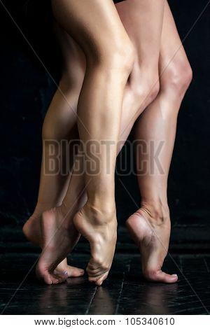 Close-up Ballerina's Legs On The Black Wooden Floor