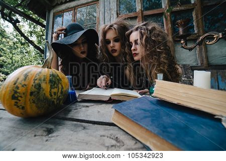 Three vintage witches perform magic ritual