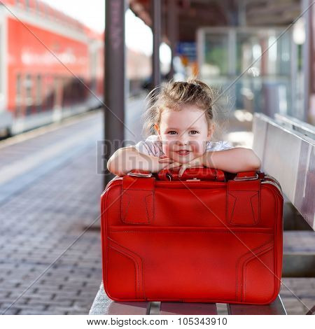 Little Girl With Big Red Suitcase On A Railway Station