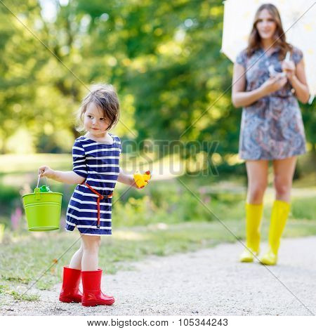 Mother And Little Adorable Kid Girl Daughter In Rain Boots