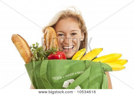 Close-up of young woman with grocery bag of healthy food and vegetables