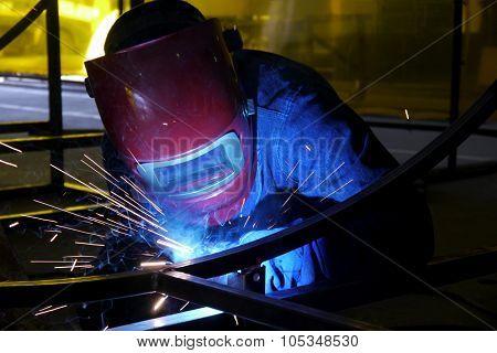 steelworker in a factory grinding metal