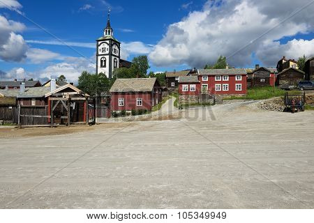 View to the traditional wooden houses and church bell tower of the copper mines town of Roros in Ro