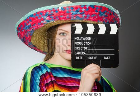 Girl in mexican vivid poncho holding clapboard against gray