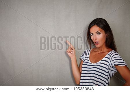Surprised Woman Pointing While Looking At Camera