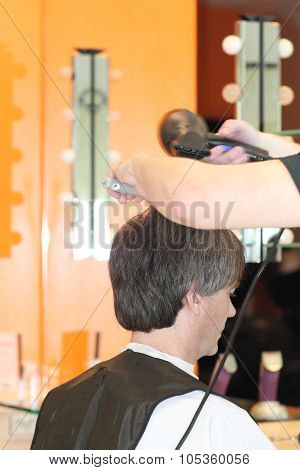 A man cuts hair in a barbershop. Master young stylist.Focus on grey hair