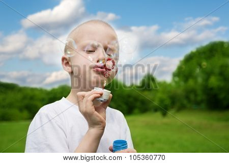 Boy inflates soap bubbles in the park.