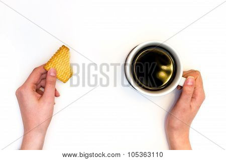 Cup of coffe with biscuit in hands