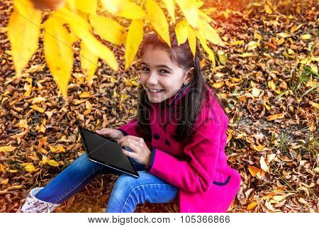 Young Girl With Digital Tablet Outside In Nature