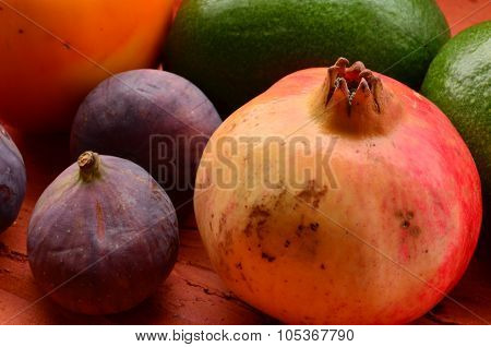 Figs, pomegranate, avocado, apples and mandarins (tangerines) on rough background