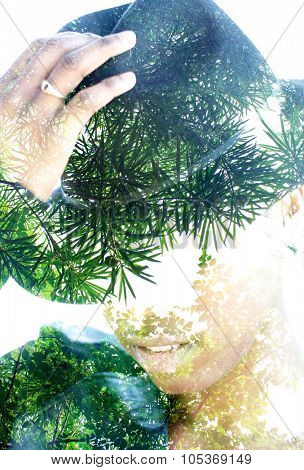 Double exposure portrait of woman with hat combined with photograph of tree