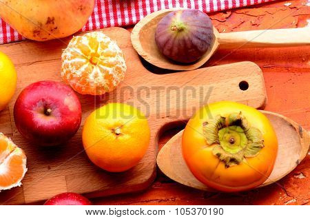 Figs, persimmon, pomegranate, apples and mandarins (tangerines) on rough background