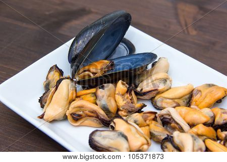 Mussels without shells on tray on wood close