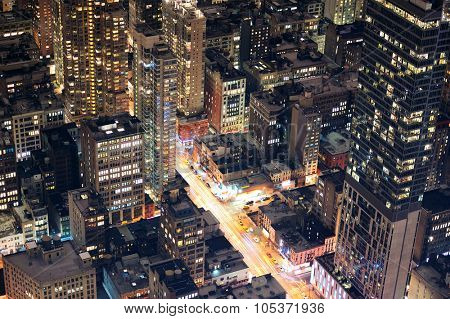 New York City Manhattan street aerial view at night with skyscrapers, pedestrian and busy traffic.