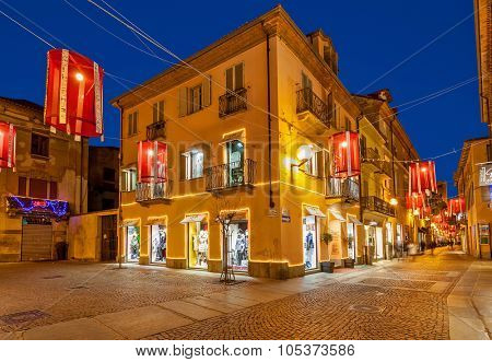 ALBA, ITALY - DECEMBER 30, 2014: Pedestrian street with shops in old town illuminated for Christmas celebrations. This area is very popular with locals and tourists visiting Alba for winter holidays.