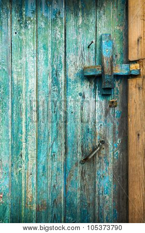 Detail of an old wooden door with scratched blue paint