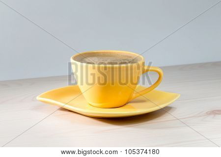 Yellow Cup Of Coffee On The Table