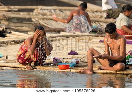 MANDALAY,MYANMAR,JANUARY 19, 2015 : Man and Women taking shower and washing dishes in a slum area at the Irrawaddy river in Mandalay, Myanmar (Burma).